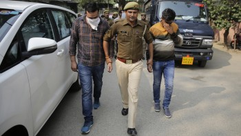 An Indian policeman escorts alleged fraudsters to be presented before media at a police station in Noida, a suburb of New Delhi (Altaf Qadri/AP)