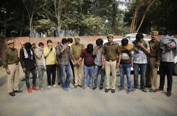 Alleged fraudsters are presented before media at a police station in Noida, a suburb of New Delhi (Altaf Qadri/AP)