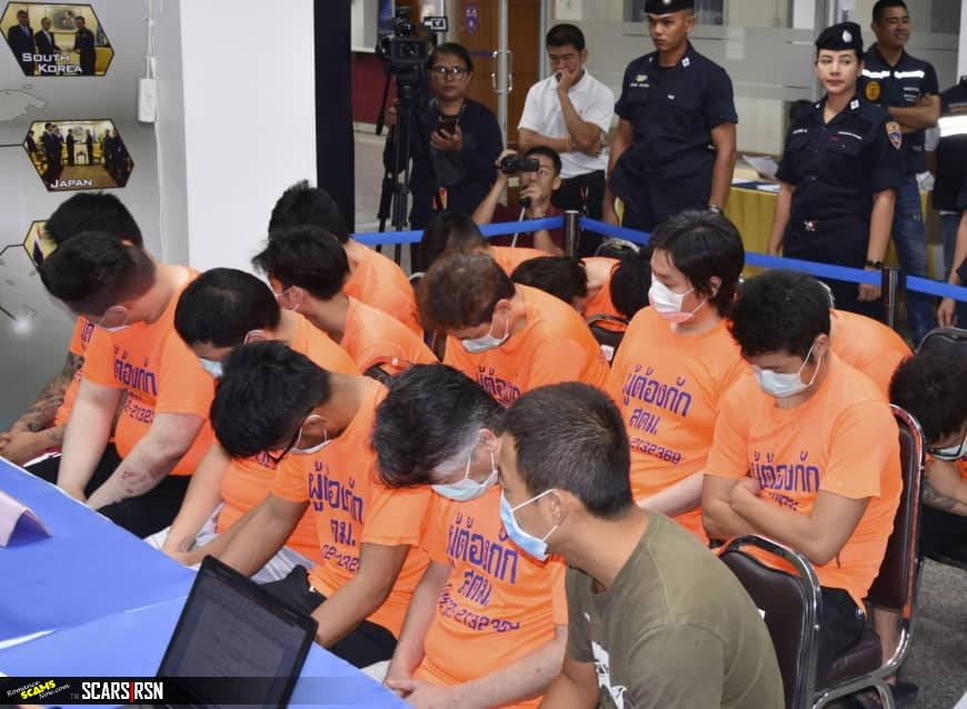 Phone home: Suspected Japanese scammers arrested in Thailand sit at an Immigration Bureau holding center in Bangkok.